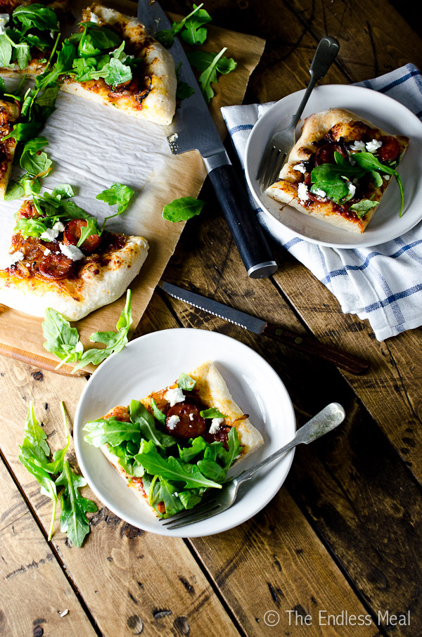 Spicy Chorizo Pizza with Caramelized Onions, Goat Cheese and Arugula