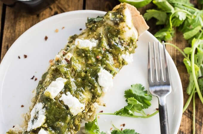 These delicious Green Chicken Enchiladas are stuffed with arroz verde (tasty green rice) and smothered in a spicy charred tomatillo sauce. It's an easy to make and healthy casserole recipe that makes a tasty weeknight dinner. Ringing in at only 250 calories per serving means you can go back for seconds or even thirds! | theendlessmeal.com
