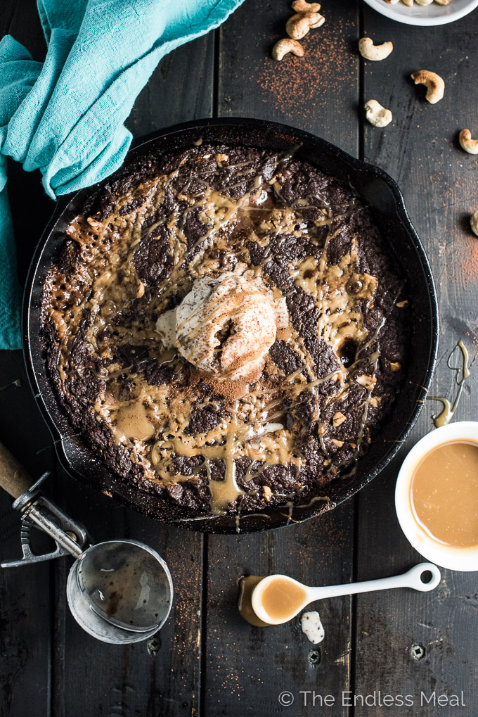 This rich and fudgy Vegan Skillet Brownie is layered with an easy to make vegan salted caramel and dotted with cashews. There's a secret ingredient in here that makes them extra delicious. | theendlessmeal.com