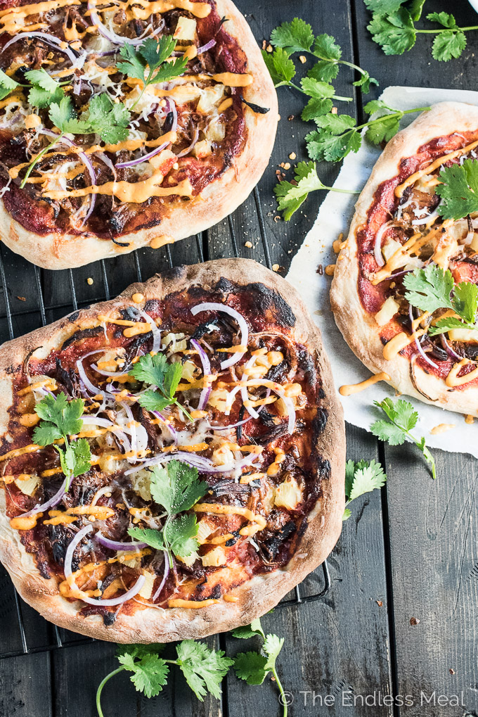 Gochujang Pulled Pork Korean Pizza is a remake of the classic ham and pineapple pizza and WAY BETTER than the original. It's served with an easy to make kimchi dipping sauce and is crazy delicious.   theendlessmeal.com