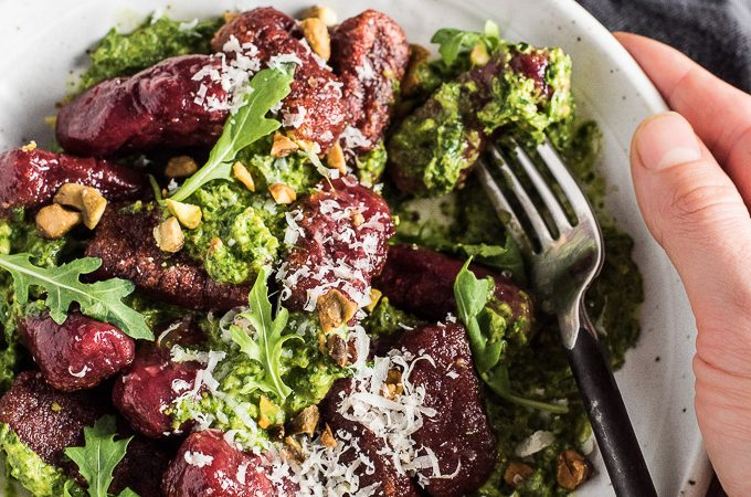 This easy to make Beet Gnocchi is as pretty as it gets. The little red clouds get nestled in some delicious arugula pesto and sprinkled with pistachios. It's festive colored and the perfect main dish recipe for holiday entertaining. | theendlessmeal.com