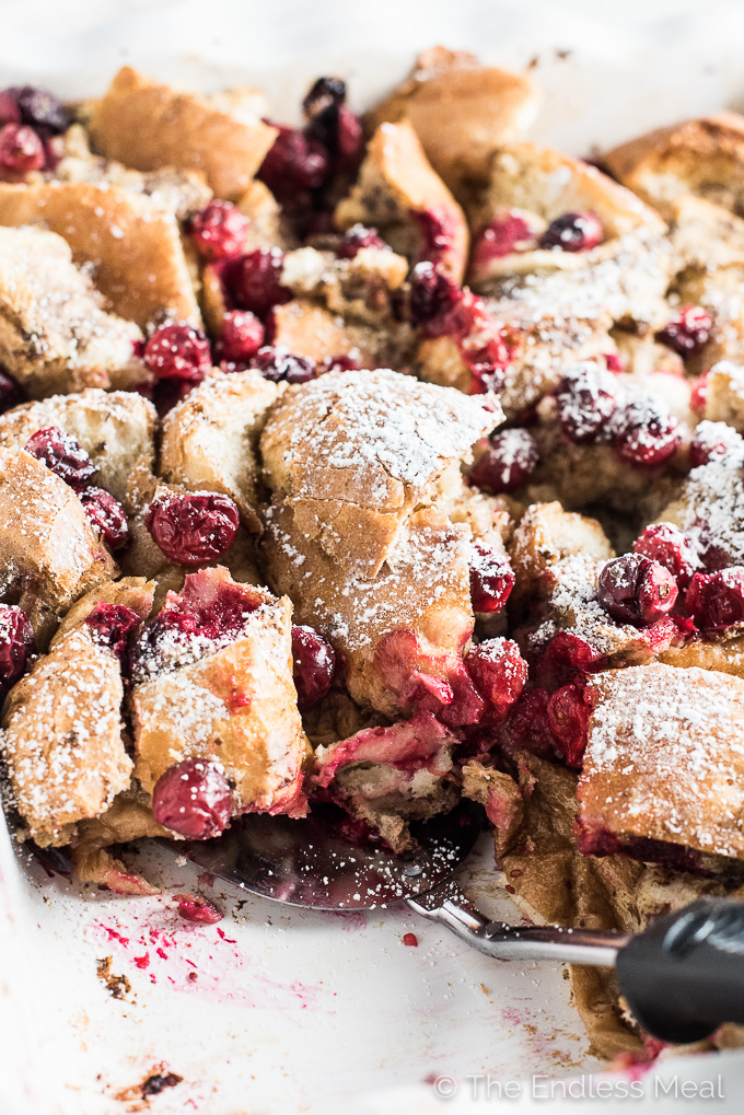 This delicious custardy Baked Vegan French Toast is dotted with cranberries and drizzled with cranberry maple syrup. It's an easy to make breakfast recipe that can be assembled a day in advance and popped in the oven before you're ready to eat. It's perfect for Christmas morning! | theendlessmeal.com