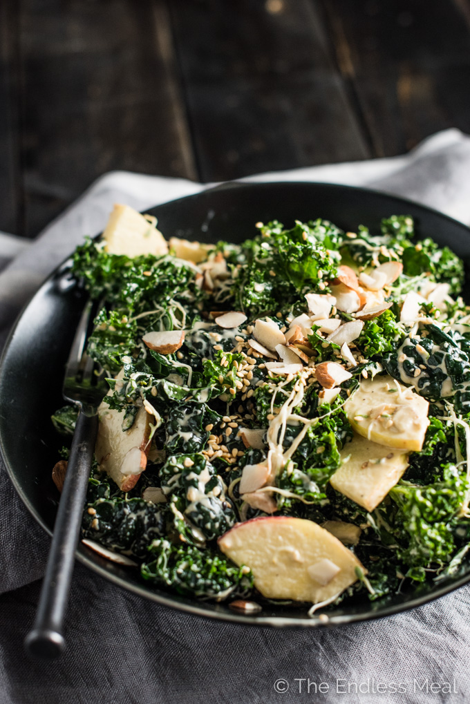 This delicious Creamy Kale Salad is tossed with a maple tahini dressing and dotted with apples, sprouts, almonds, and sesame seeds. It's an easy to make side dish recipe that is naturally vegan + gluten-free and can easily be made paleo. | theendlessmeal.com