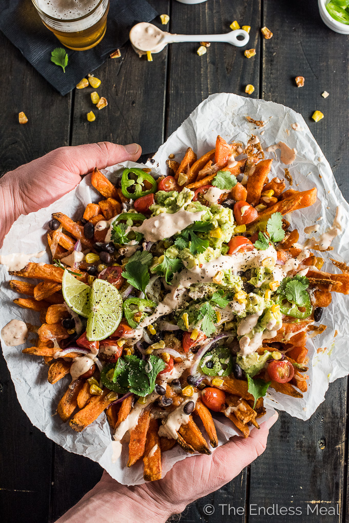 Mexican Nacho Fries, you ask? That's right! These babies are everything food truck dreams are made of: sweet potato fries smothered in melted white cheddar, roasted corn, black beans, cherry tomatoes, jalapenos, red onions, and guacamole then drizzled with creamy/ spicy chipotle crema. Add this recipe to your must-make Super Bowl/ game day party list; your friends will love you for it. | theendlessmeal.com