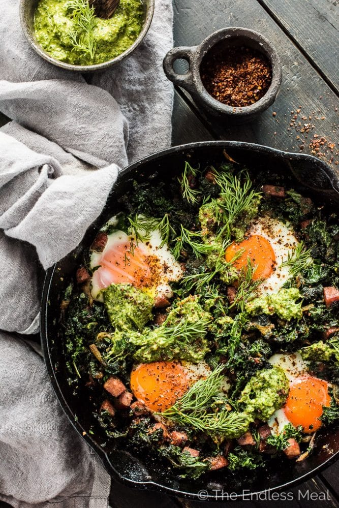 This easy to make green shakshuka is a playful take on a Green Eggs and Ham Recipe. The eggs are nestled into caramelized onions, farmer's sausage, and kale and topped with a delicious lemony dill pesto. This healthy breakfast recipe is bursting with flavor and naturally paleo + Whole30 approved. | theendlessmeal.com
