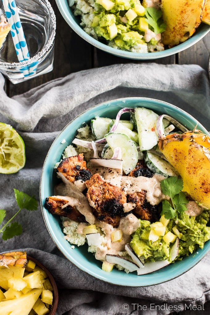 These tropical Thai Chicken Burrito Bowls are crazy delicious. They're layered with coconut cauliflower rice, grilled Thai chicken, pineapple guacamole, cucumber salad, and drizzled with satay sauce. It's a healthy dinner recipe that is gluten-free + paleo + Whole30 compliant. | theendlessmeal.com